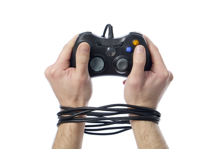 wired hands with joypad meaning videogame addiction Stock Photo