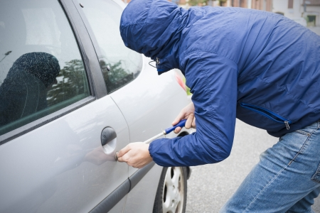 felony: thief stealing automobile car at daylight street in city Stock Photo
