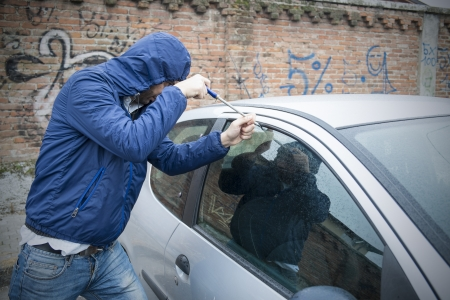 identity thieves: thief stealing automobile car at daylight street in city Stock Photo