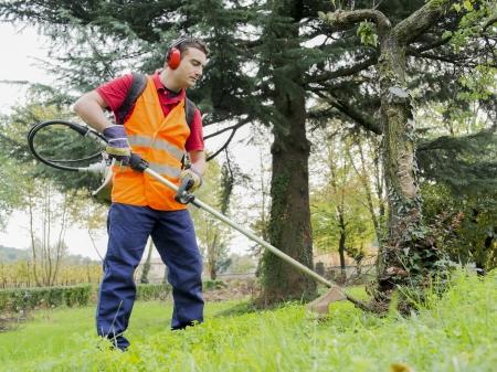 Mann mit Gehörschutz Mähen von Gras im Hinterhof mit Benzin-Heckenschere