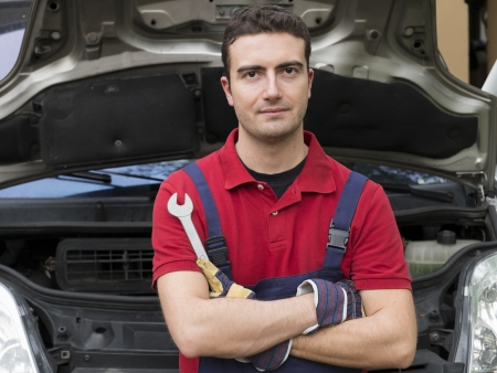portrait of a mechanic with arms folded in auto repair shop