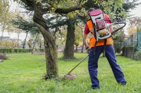 man met gehoorbescherming maaien van gras in de achtertuin met benzine heggenschaar Stockfoto
