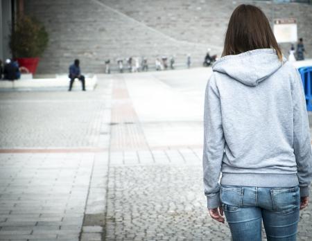 sudadera: chica solitaria en la ciudad en peligro Foto de archivo