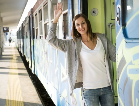hand rails: young woman leaving at the departure train station platform Stock Photo