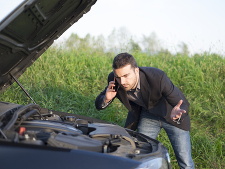 gass: man talking on a cell phone by a broken car