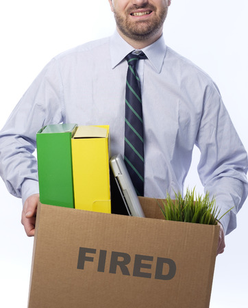 belongings: Fired businessman holding box with personal belongings isolated on white background. Stock Photo