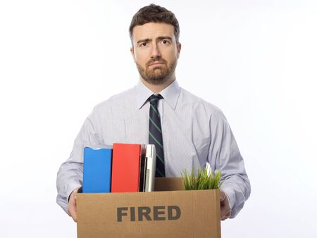 unemployed dismissed: Fired businessman holding box with personal belongings isolated on white background. Stock Photo