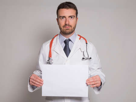 copysapce: doctor holding a white copyspace billboard isolated on gray background