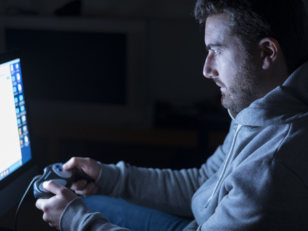 videogame: Young adult playing with video-game during night