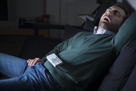 Hombre durmiendo y roncando en frente de la televisión en el sofá Foto de archivo