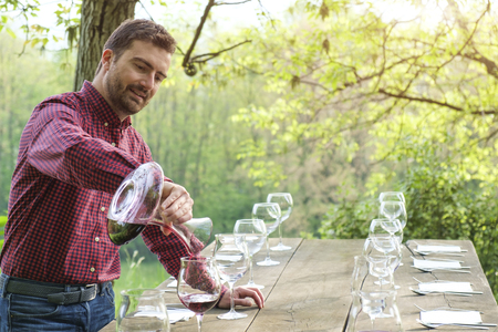 taster: wine taster and wine glasses on a wooden table outdoor in the countryside