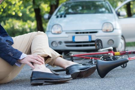 アスファルトの上の自転車事故後痛男 写真素材
