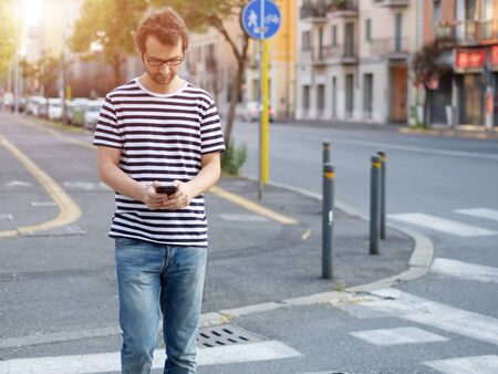 inattention: portrait of young adult man crossing inattentively the street distracted by his phone