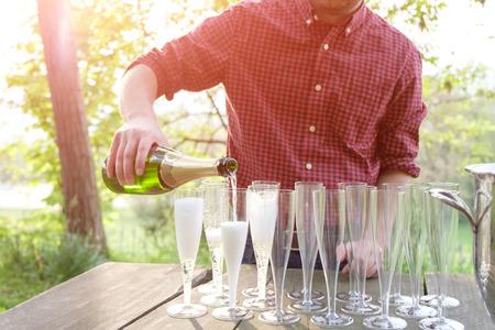 Mann gießt Champagner in Gläser Flöten