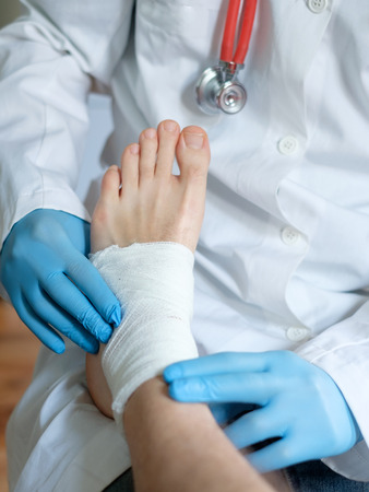 foot doctor: close up of doctor bandaging one injured foot after an accident Stock Photo