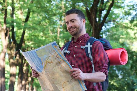 the right path: young urban traveler consulting a map to find the right path