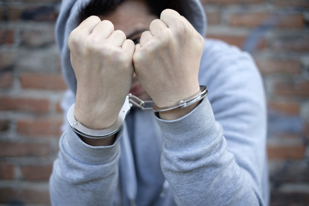 portrait of handcuffed man with face hidden by sweatshirt hood
