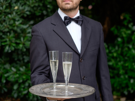 half dressed: professional waiter in uniform is serving champagne