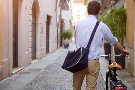 rolled up sleeves: Picture of a young smiling business man on a bicycle on his way home from work while the sun is setting. He has a more relaxed style with the sleeves of his blue shirt rolled up and he is also wearing a blue bag on his shoulder. In the background theres  Stock Photo
