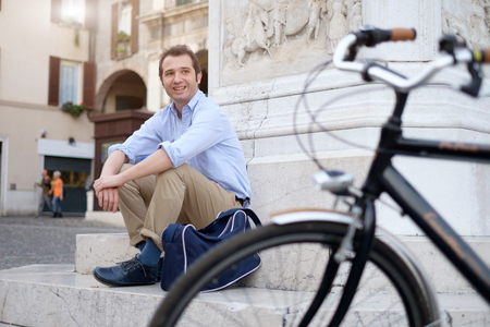 his shirt sleeves: Picture of a young smiling business man on a bicycle on his way home from work while the sun is setting. He has a more relaxed style with the sleeves of his blue shirt rolled up and he is also wearing a blue bag on his shoulder. In the background theres  Stock Photo