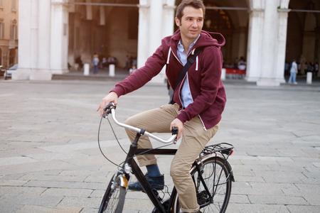 Bild eines jungen Studenten Mann auf einem Fahrrad auf dem Heimweg von der Arbeit, während die Sonne einstellt. Er hat eine entspannteres. Im Hintergrund gibt es einen Platz in der Stadt mit einigen städtischen Gebäuden.