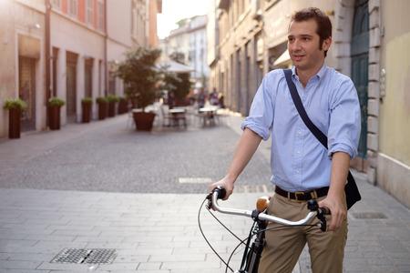 Bild eines lächelnden jungen Geschäftsmann auf einem Fahrrad auf dem Heimweg von der Arbeit, während die Sonne einstellt. Er hat eine entspanntere Art mit dem Ärmel seines blauen Hemd aufgerollt und er ist auch eine blaue Tasche auf der Schulter tragen. Im Hintergrund gibt es
