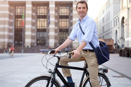 Bild eines lächelnden jungen Geschäftsmann auf einem Fahrrad auf dem Heimweg von der Arbeit, während die Sonne einstellt. Er hat eine entspanntere Art mit dem Ärmel seines blauen Hemd aufgerollt und er ist auch eine blaue Tasche auf der Schulter tragen. Im Hintergrund gibt es Standard-Bild