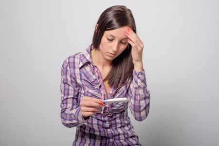 unplanned: Sad young Woman with pregnancy test