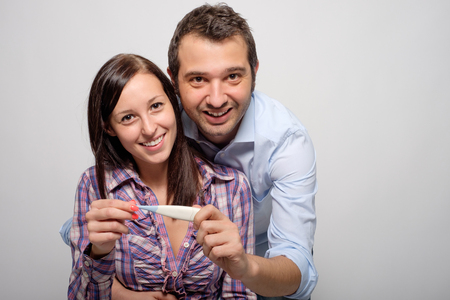 test result: Happy young lovers couple after positive pregnancy test result