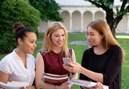 learnt: Three young females  friends all together looking at mobile phone Stock Photo