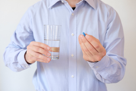Man taking a pill with water