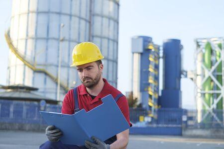 topografo: trabajador fuera de una fábrica trabajando vestido con equipo de seguridad guardapolvos
