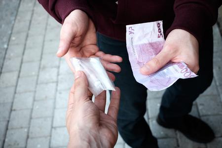 drug addict: Pusher and drug addict exchanging money and drug
