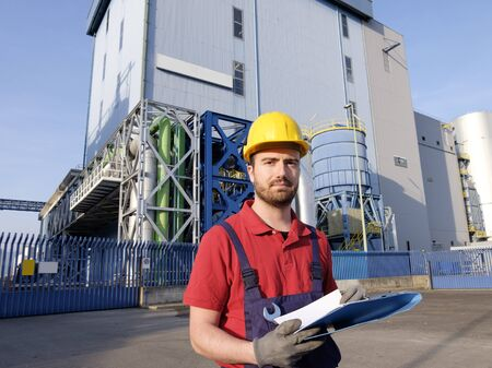 laborer outside a factory working dressed with safety overalls equipment Stock Photo