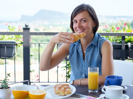 Cheerful woman having a continental breakfast