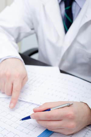 bp: Doctor checking an electrocardiogram papers