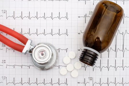 Top view of stethoscope and pills on an electrocardiogram