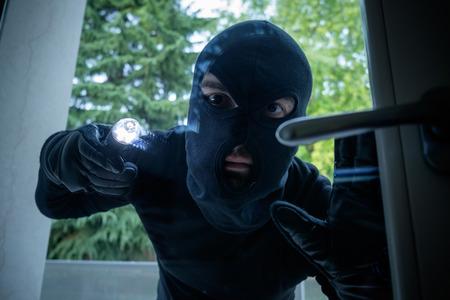 malefactor: Burglar wearing a balaclava looking through the house window