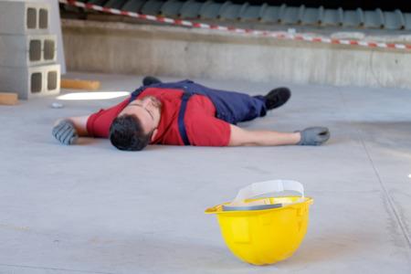 emergency vest: Dramatic on-the-job injury main focus on the yellow helmet Stock Photo