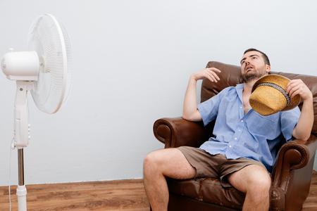caliente: hombre enrojecida sensación de calor en la parte frontal de un ventilador Foto de archivo