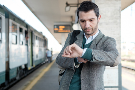 standing man waiting for the train in a train station platform Stock Photo