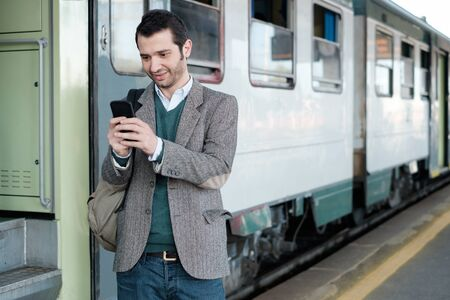 businessman waiting call: standing man calling on the phone waiting for the train in a train station platform