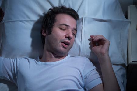 cansancio: El hombre est� durmiendo en su cama por la noche