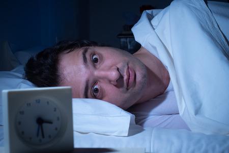 不眠症のための強調した男性は、彼のベッドで眠ることができません。