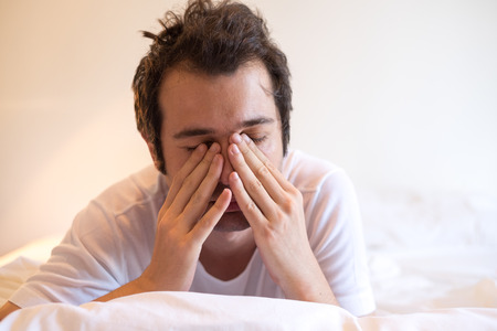 aggravated: Man lying in bed and waking up in the morning Stock Photo