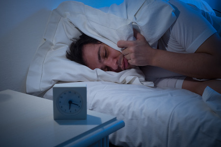 aggravated: Man lying in bed turning off an alarm clock Stock Photo