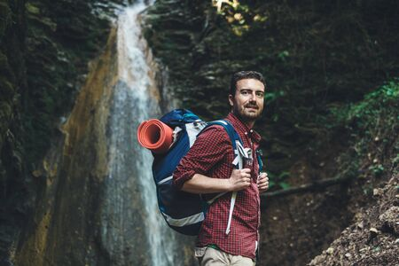 Man next to a waterfall after mountain trekking