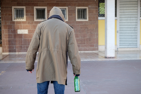 walking alone: Homeless drunk and  alcohol addicted walking alone