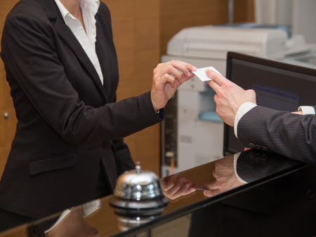 desk clerk: Businessman is arrived in hotel and is checking-in Stock Photo
