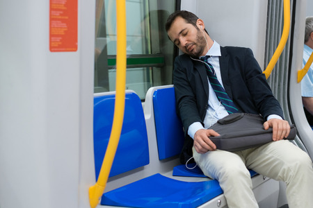 Tired businessman sleeping on the underground metro Imagens